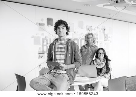 Portrait of creative businessman holding digital tablet with female colleagues in background