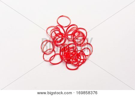 Red rubber bands on white background. Office supplies. Assortment of stationery.