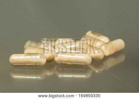 Bunch of probiotics capsules on gray background