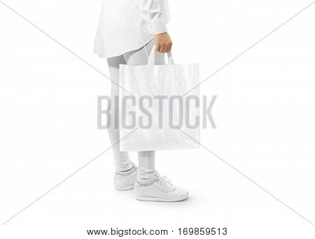 Blank white plastic bag mockup holding hand. Woman hold carrier sac mock up with loop handles. Plain bagful branding template. Shopping carry package in persons arm. Packet for logotype branding.