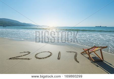 2017 written in sand write on tropical beach with Deck chair.