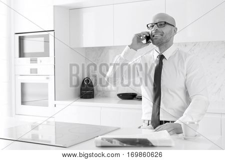 Mid adult businessman on call at kitchen counter
