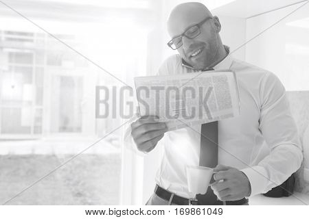 Mid adult businessman on call while holding newspaper and coffee cup at home