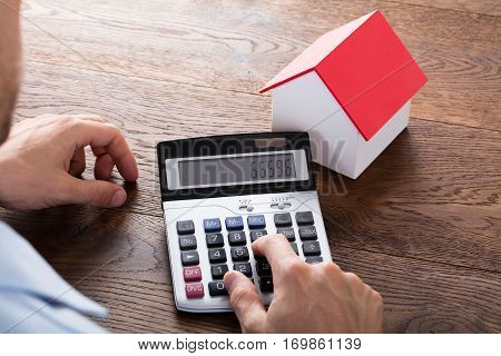 Close-up Of A Person Hand Doing Property Tax Calculation Using Calculator Of House Model