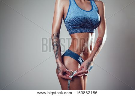 Athletic slim woman with tattoo measuring her hips by measure tape on grey background.