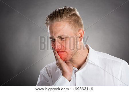 Young Man Suffering From Toothache Against Grey Background