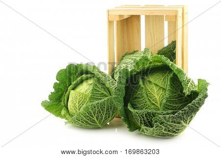 fresh green cabbages in a wooden crate on a white background