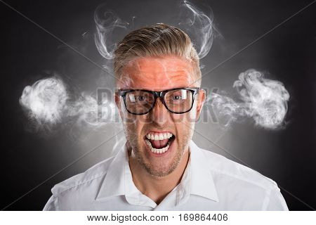 Furious Young Businessman With Red Forehead And Smoke