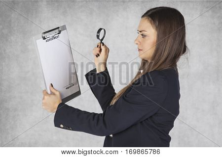 Business Woman Uses A Magnifying Glass To Read The Agreement