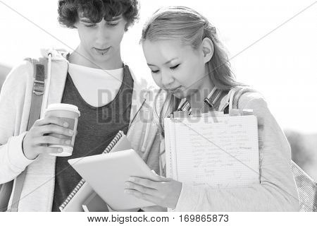 Male and female friends using digital tablet at college campus