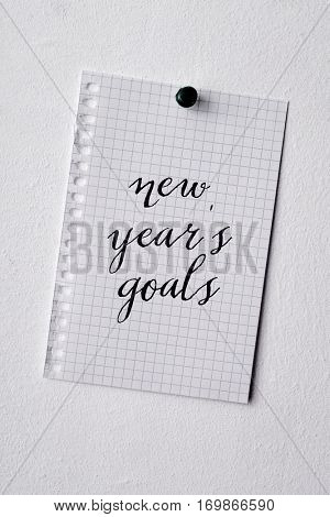 closeup of a piece of paper with the text new years goals written in it pinned in a white wall with a push pin