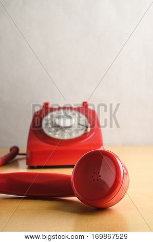 Eye level shot of a retro red 1960s to 70s British style telephone with receiver off the hook and in close up foreground. Dial base in soft focus background.