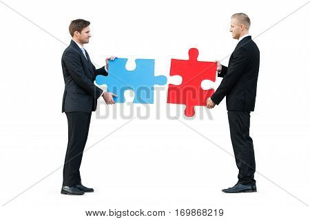 Two Businessmen Solving Jigsaw Puzzle While Standing On White Background