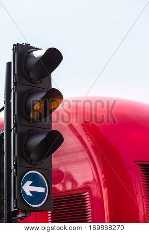 Traffic light with illuminated yellow signal lamp and white arrow on blue surface for driving direction to the right, back of red bus at the background (copy space)