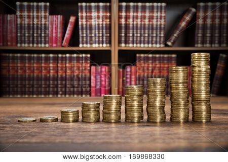 Close-up Of A Stacked Coins On Wooden Desk In Courtroom