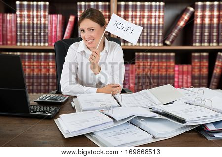 Female Accountant Holding Help Flag With A Pile Of Folders