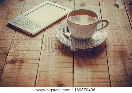 A cup of tea and an ebook reader on a rustic wood table by a window