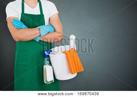 Close-up Of A Janitor Holding Cleaning Equipments On Gray Background