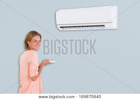 A Happy Young Woman Operating Air Conditioner With Remote Control At Home