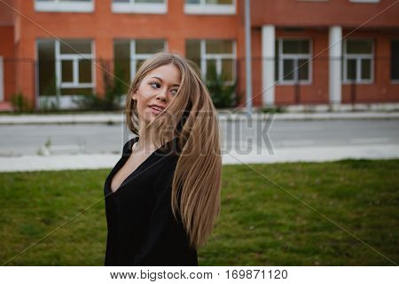 Pretty blonde girl with a beautiful long an grass of background