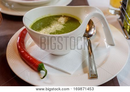 Fresh Spinach cream soup with chili in a white bowl