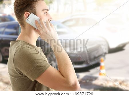 Young man talking on phone after car accident. Traffic safety concept.