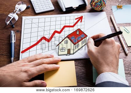 Close-up Of Businessperson Hand Drawing Property And Real Estate Concept On White Paper