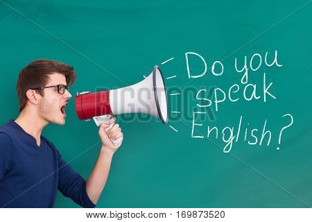 Young Man Doing Announcement Of English Speaking Using Megaphone On Blackboard