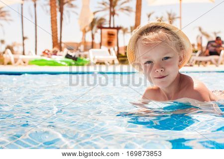 Portrait of cute happy little girl having fun in swimming pool. Active summer vacation on the beach.