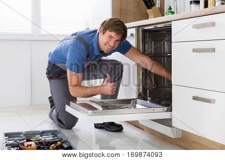 Repairman Examining Dishwasher With Toolbox In Kitchen
