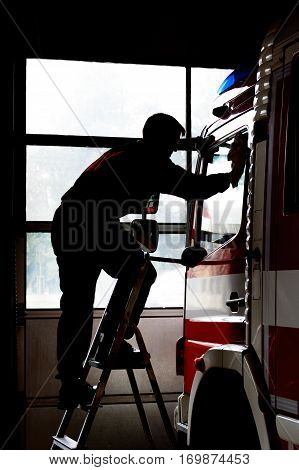 Firefighter cleans firetruck. Maintenance of fire equipment. Life at the fire station.