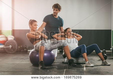 Two girls exercising at the gym with a personal trainer.