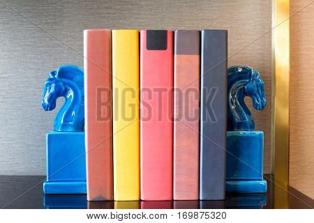 elegant book ends and books on table in modern study