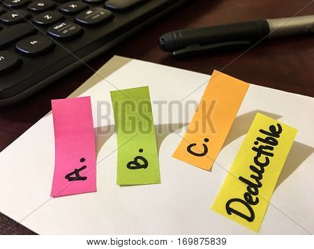 Confusing insurance coverage words ABC's of insurance deductible written on a notepad as a colorful checklist of things to ask what's covered by policy to an insurance company or representative about taxes, finance, home or car insurance policy terms and