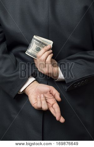 Detail of a businessman standing and holding his hands behind his back holding bunch of money in one hand and fingers crossed on another one. Selective focus