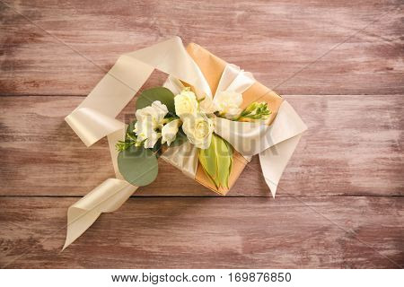 Handcrafted gift box with flowers on wooden table