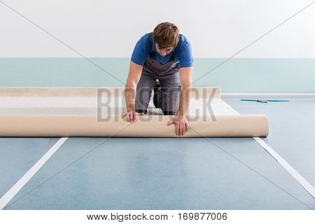Portrait Of Happy Young Man Laying Carpet On Floor At Home