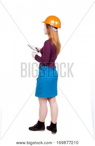 Backview of business woman in construction helmet stands and enjoys tablet or using mobile phone. Isolated over white background. Young woman engineer working on tablet. Engineer scorekeeper at work