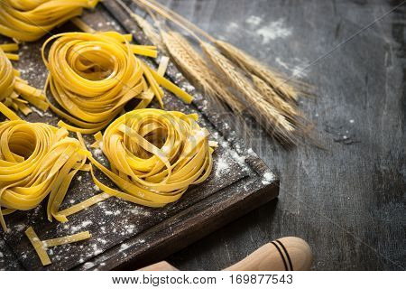 Fresh italian raw homemade pasta tagliatelle at wooden table. Italian food background.