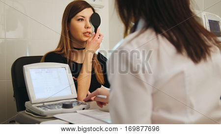 Young woman doing eye test with optometrist in medical center, close up