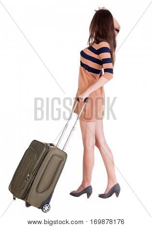 Back view of stylishly dressed brunette woman with suitcase looking up. Standing young girl. Rear view people collection.  Isolated over white background. languid girl in heels looks into the distance
