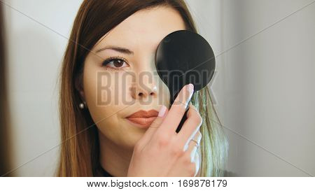 Ophthalmology medical, health, concept - beautiful girl checks vision in an ophthalmologist with one eye closed, telephoto