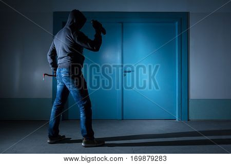 Rear View Of A Thief With Flashlight And Crowbar Standing Outside The Door