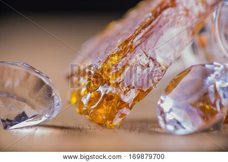 Piece of cannabis oil concentrate aka shatter with glass rig and diamonds over wood background