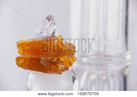 Piece of cannabis oil concentrate aka shatter over a glass rig isolated over white background