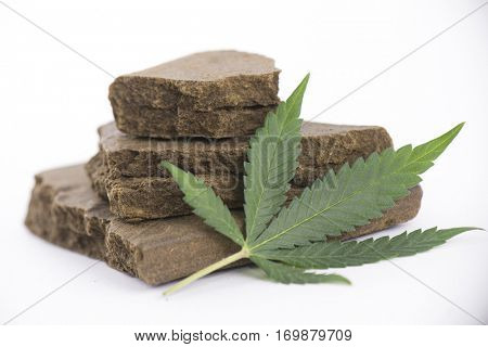 Blocks of hashish, a medical marijuana concentrate isolated on white with cannabis leaf