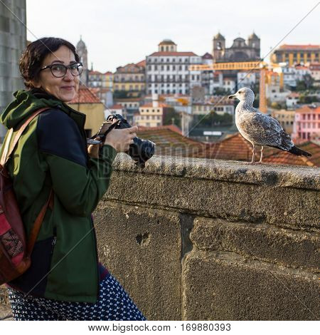Woman tourist taking pictures a seagull on a background of Porto old town, Portugal.