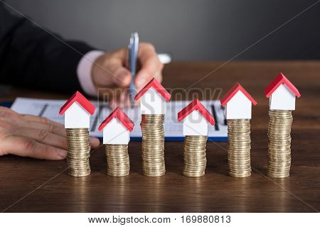 Close-up Of A Businessman Calculating Tax In Front Of Stacked Coins And House Models