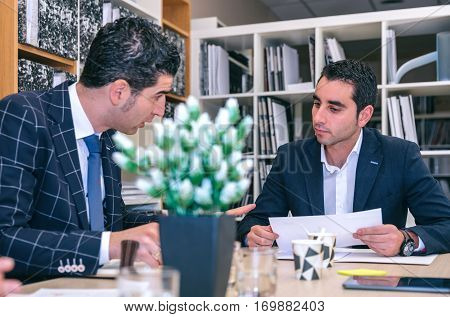 Two businessmen talking in a meeting sitting at table in company headquarters