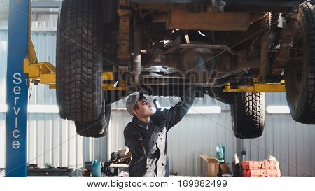 Car service - a mechanic checks the suspension of SUV, wide angle, horizontal